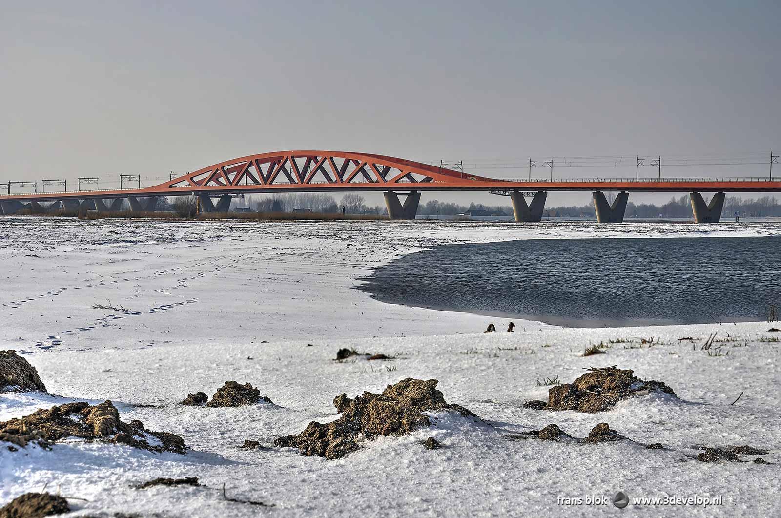 Foto van de rode Hanzeboog-spoorbrug over de IJssel bij Zwolle, gezien vanuit een besneeuwd uiterwaardenlandschap