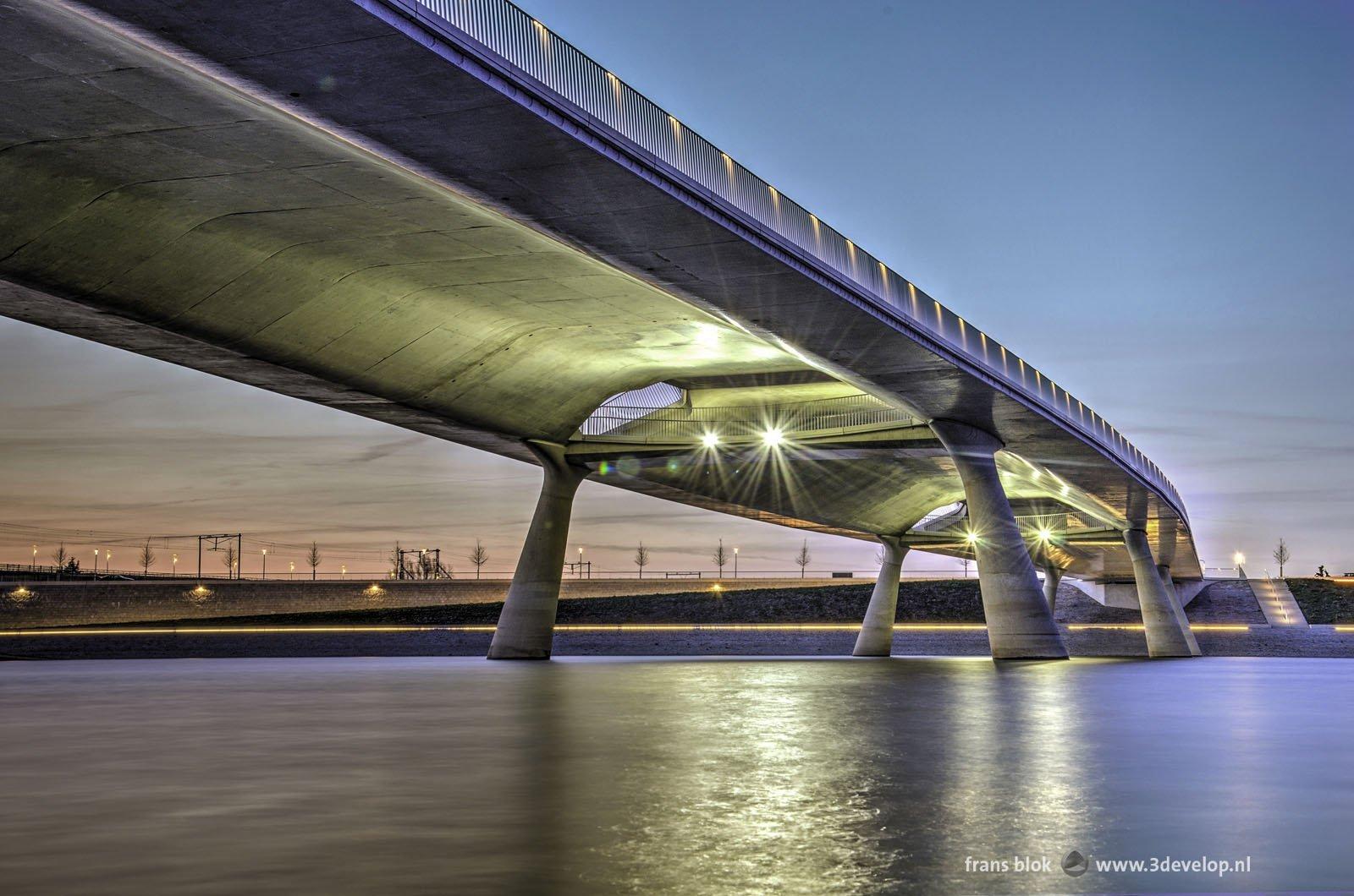 Promenadebrug de Lentloper over de Spiegelwaal bij Nijmegen, gefotografeerd vanaf het eiland Veur-Lent tijdens het blauwe uur