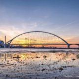 Zonsondergang achter de nieuwe stadsbrug de Oversteek in Nijmegen gezien vanaf een strandje langs de Waal