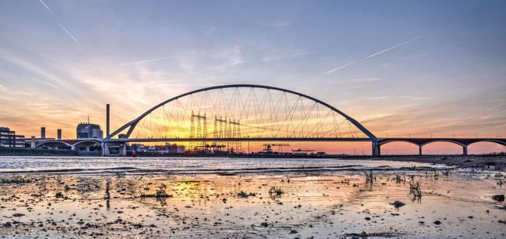 Sunset behind the new city bridge De Oversteek (The Crossing) in Nijmegen as seen from a little beach on the banks of the river Waal