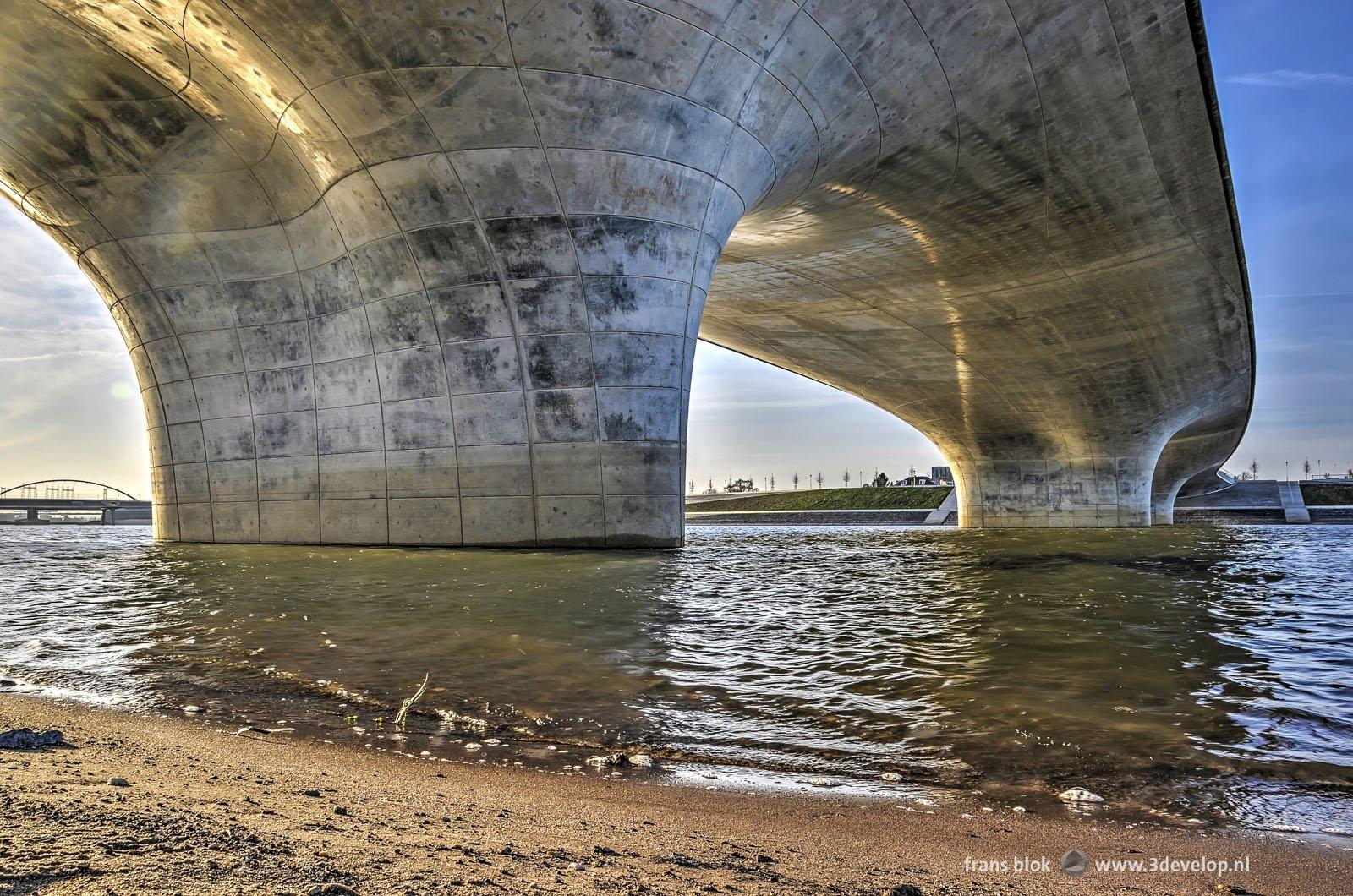 Foto vanaf het strand langs de Spiegelwaal bij Nijmegen op de stoere betonnen vormen van de Verlengde Waalbrug