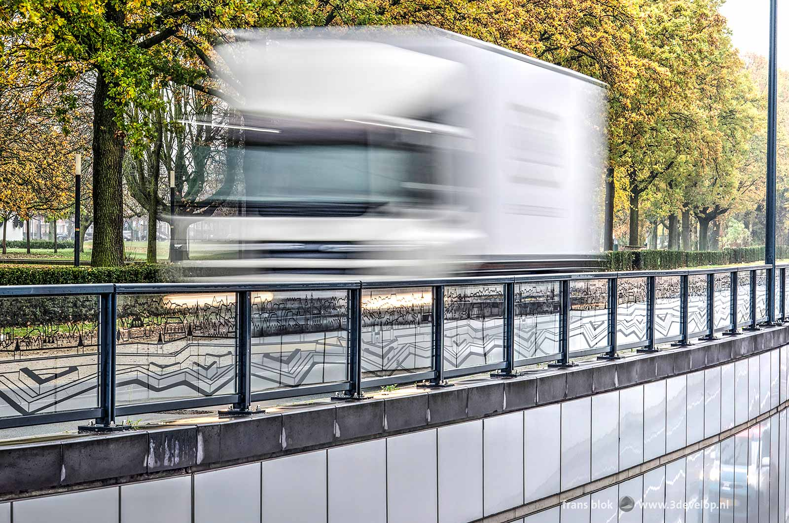 Vrachtwagen passeert de glaspanelen met prints van de vestingwerken langs de onderdoorgang van het Koninginneplein in Venlo