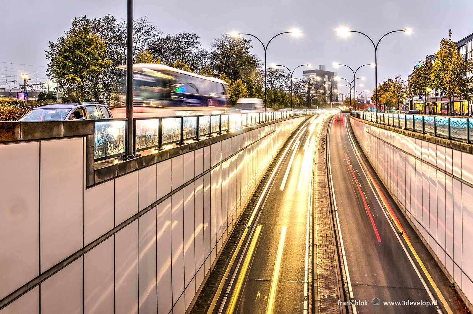 Lichtstrepen van auto's in de onderdoorgang onder het Koninginneplein in Venlo bij avond met langzaamrijdend verkeer naast de tunnel.