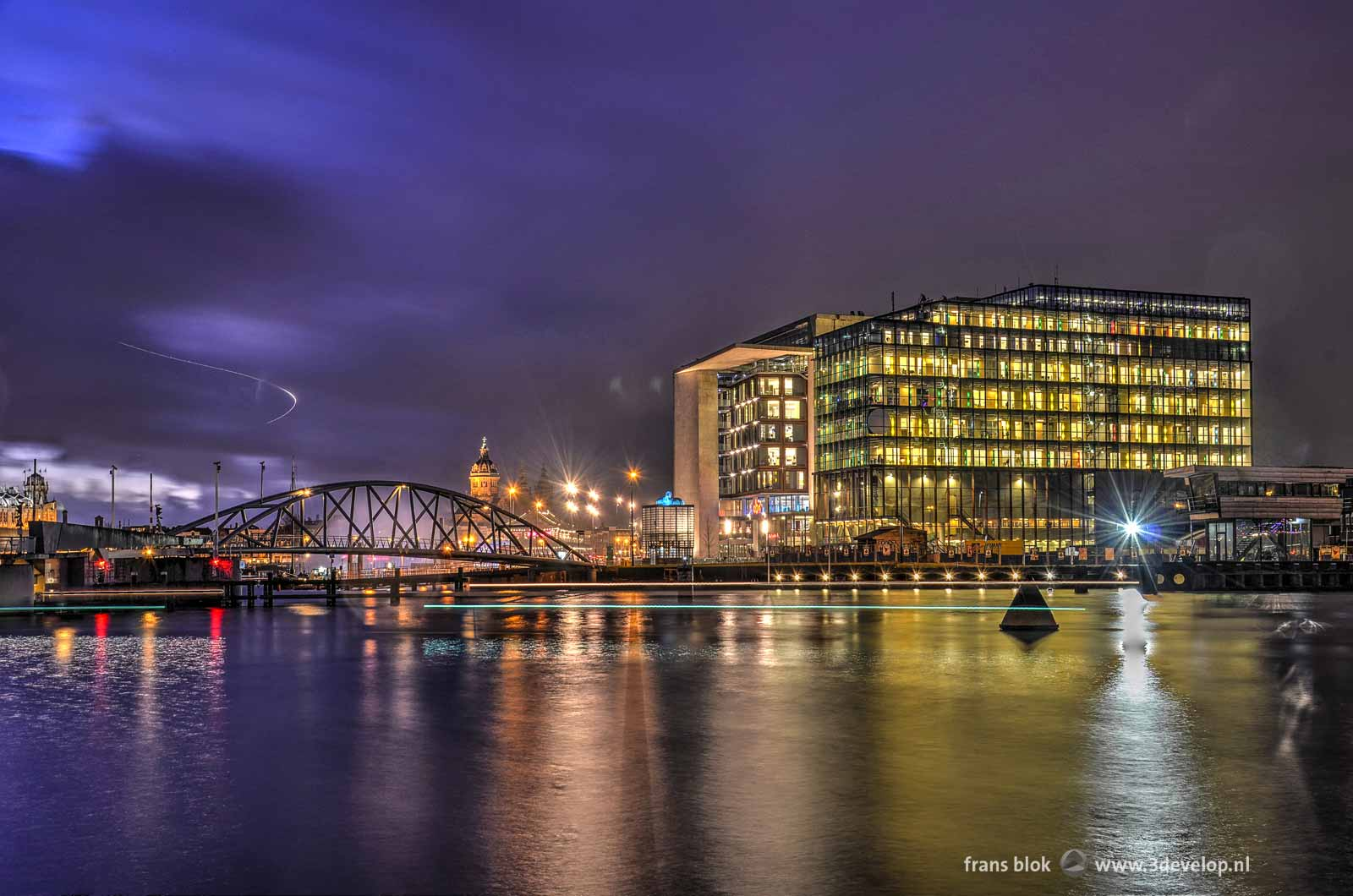 Photo taken during the blue hour after sunset at the Eastern Dock in Amsterdam, featuring the conservatory, the Library and Saint Nicholas Church