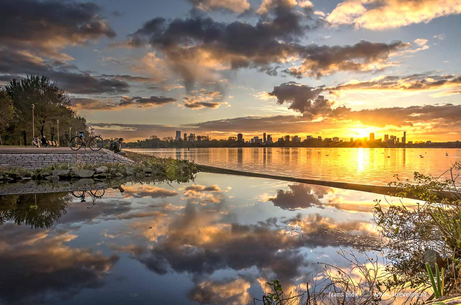 Sunset above the Rotterdam skyline seen from the banks of Lake Kralingen near Minangkabau House