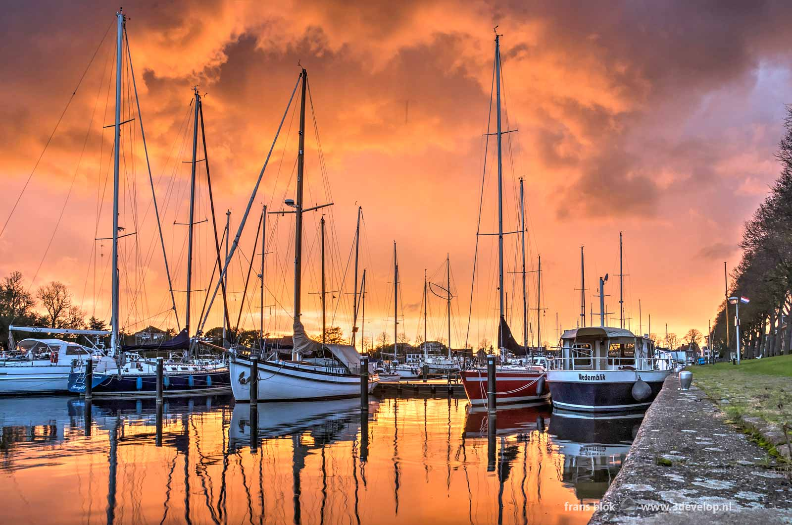 Spectacular red sunset above the sailing yachts in the marina at Medemblik's western harbour in the Netherlands