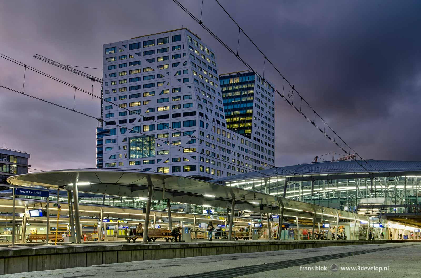Foto gemaakt vanaf het perron op station Utrecht Centraal tijdens het blauwe uur, met de perronoverkappingen, de stationshal en het Stadskantoor.