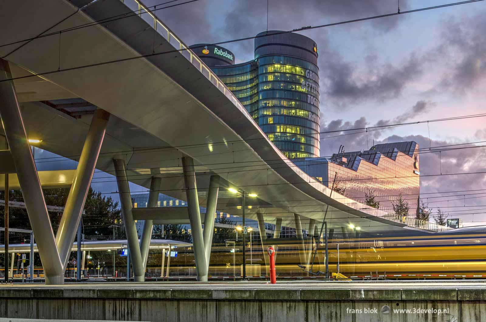 Foto gemaakt vanaf het perron op station Utrecht Centraal tijdens het blauwe uur, met de nieuwe voetgangersbrug, het gebouw van de Rabobank en een passerende trein.