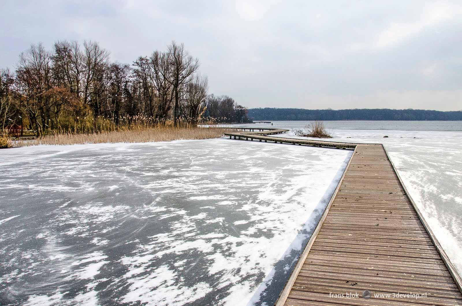 Wooden walkways across the frozen and snow-covered Lake Kralingen in Rotterdam