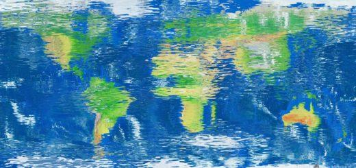 Wereldkaart gespiegeld in een reflecterend en licht golvend wateroppervlak