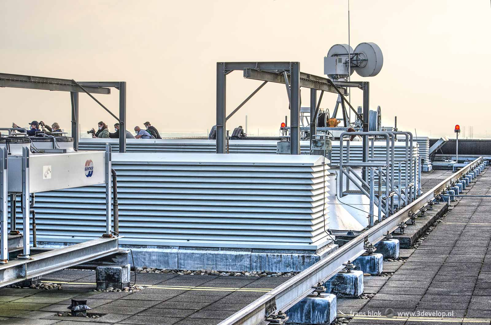 The machinery on the roof of the Delftse Poort building in Rotterdam where a group of photographers is taking pictures