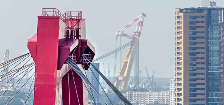 Image made with a telephoto lens showing one of the pylons of willems Bridge in Rotterdam with in the background a residential tower and a large crane in the harbour