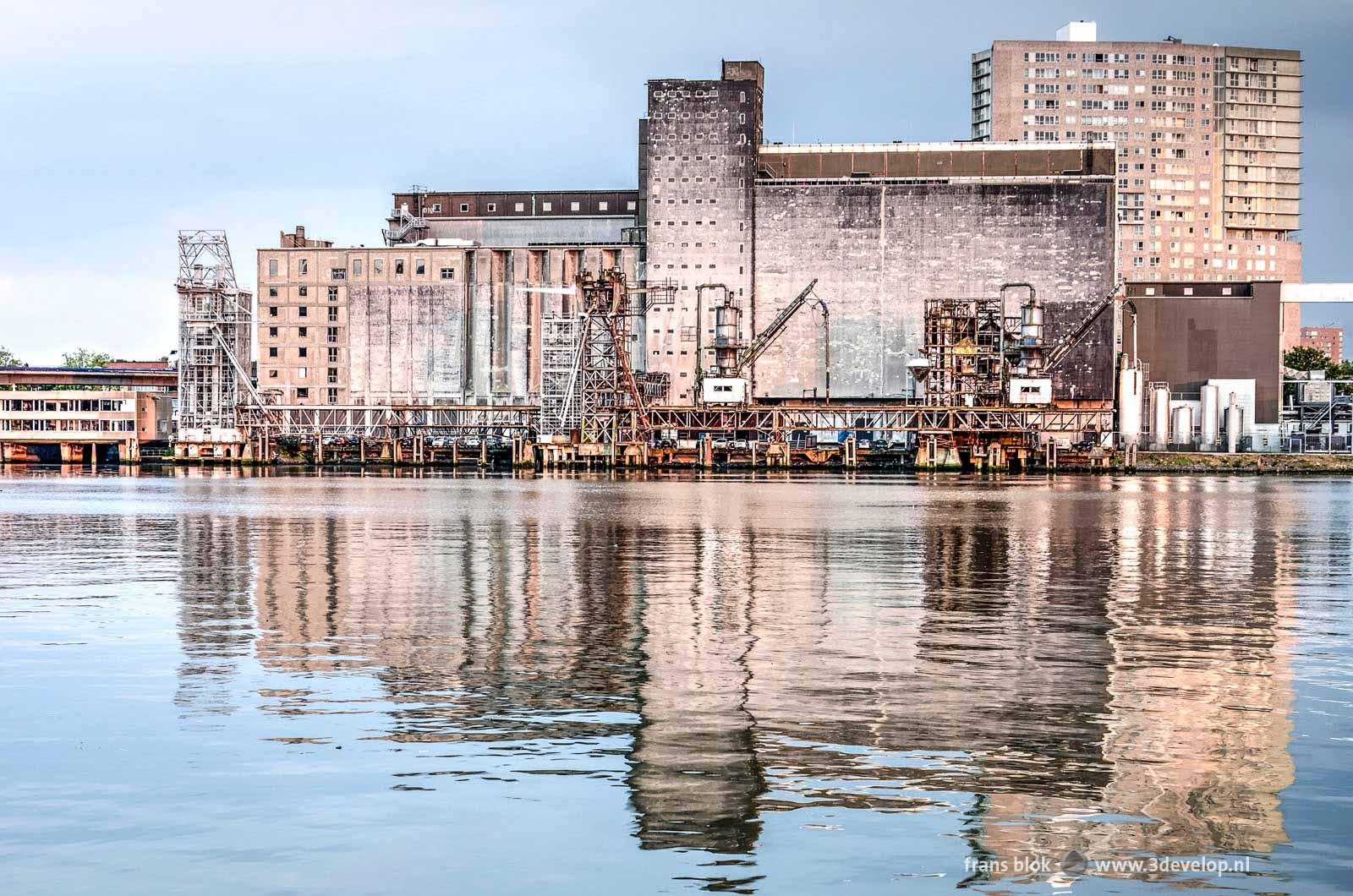 De Maassilo in Rotterdam, spiegelend in het bijna rimpelloze water van de Maashaven, gezien vanaf de kade in Katendrecht
