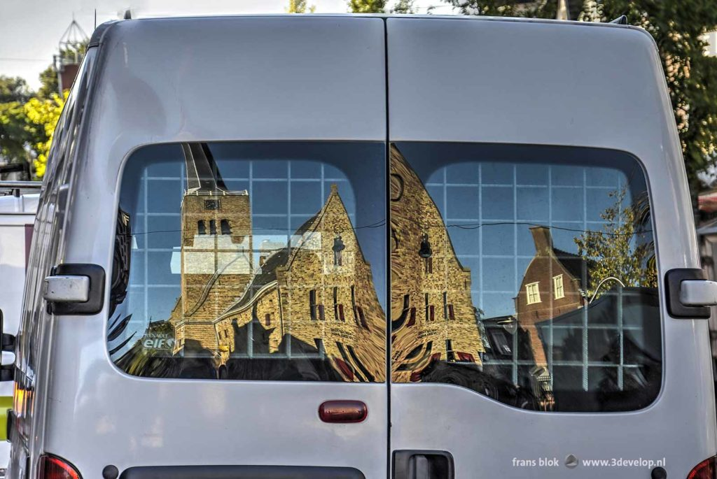 De Martinikerk in Franeker, weerspiegeld in het achterraam van een witte bestelbus