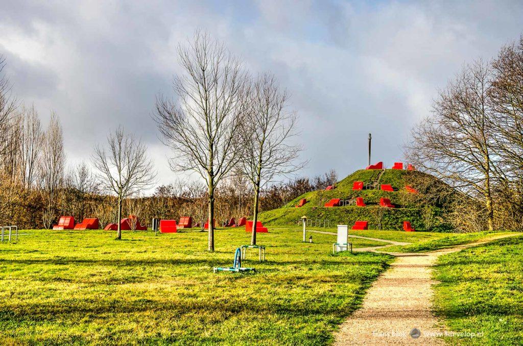 Chill Hill, een kunstmatige heuvel in park Heerlijkheid Hoogvliet met rode chillelementen en uitzicht op de industrie