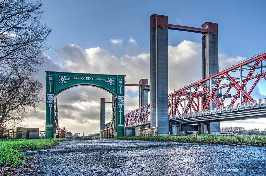 Een portaal van de oude Spijkenisserbrug met op de achtergrond de nieuwe brug