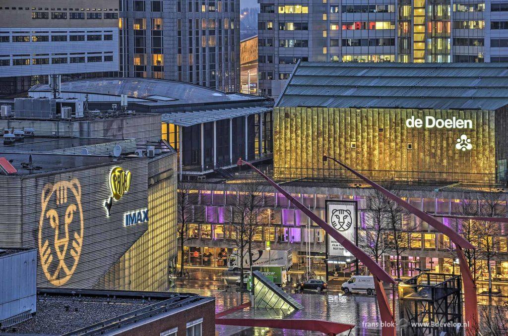 Avondfoto, genomen van een hoog standpunt, van het Schouwburgplein, de Pathe-bioscoop en de Doelen met een ontsierende witte vrachtwagen en witte bestelbus