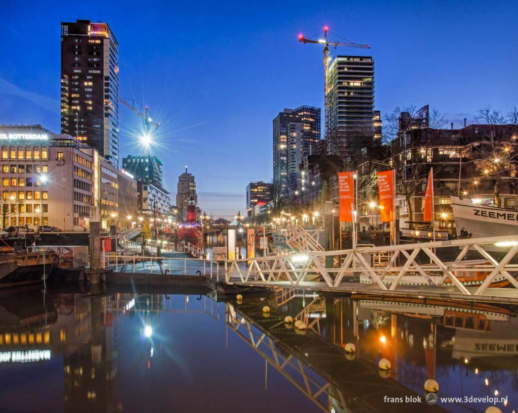 The floating pontoon bridge across Leuvehaven harbour near the Maritime Museum in Rotterdam during the blue hour before sunrise