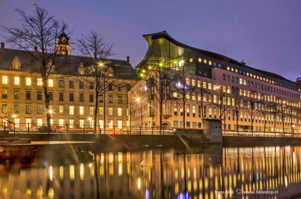 Het stadhuis en het politiebureau in Rotterdam weerspiegelend in het water van de Delftsevaart tijdens het blauwe uur op een ochtend in januari