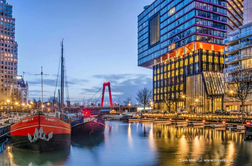 Wijnhaven harbour in Rotterdam with residential building The Red Apple, some historic barges and in the background Willems bridge during the blue hour before sunrise