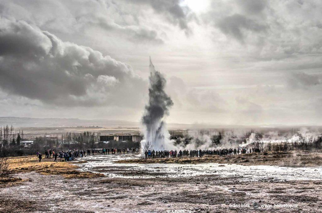 De Strokkur-geiser in IJsland, op een steenworp afstand van de historische Geysir-geiser, tijdens een uitbarsting gadegeslagen door honderden toeristen