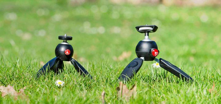 Twee verschillende ministatiefjes van de firma Manfrotto in een grasveld met madeliefjes