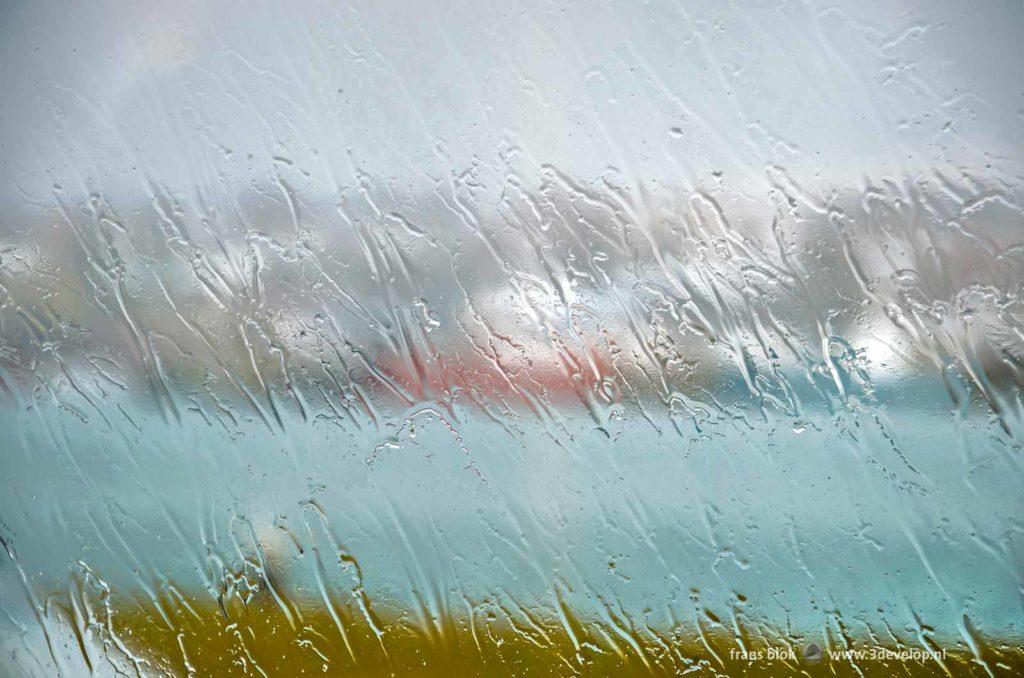 Regendruppels trekken strepen op het glas tijdens een regenachtige dag in IJsland met op de achtergrond de haven van Hafnarfjordur