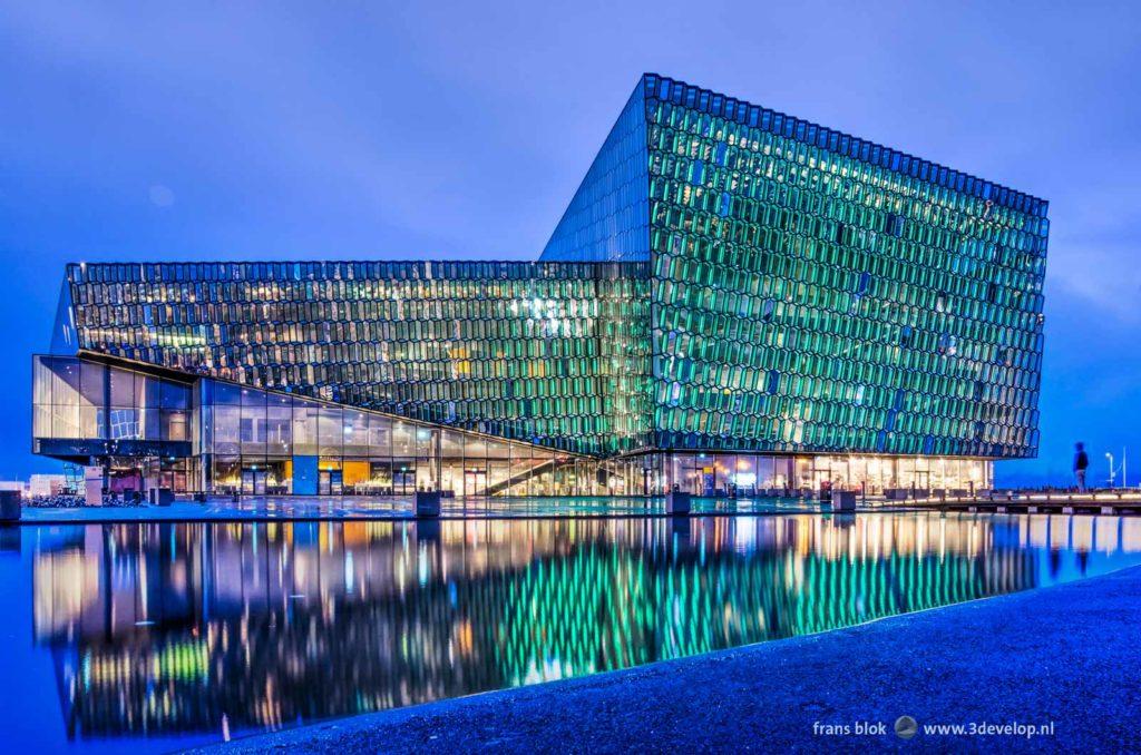 Concert- en congresgebouw Harpa in Reykjavik, IJsland, spiegelend in een waterpartij tijdens het blauwe uur na zonsondergang