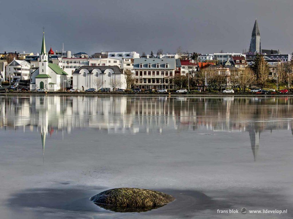 Twee kerken, Hallgrimskirkja en Frikirkja, spiegelen in het smeltende ijs van het Tjornin-meer in Reykjavik aan het eind van de winter