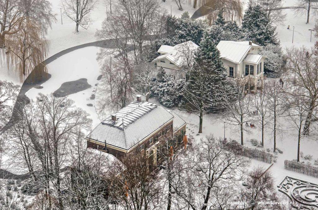 Het Heerenhuis en het Koetshuis in het Park in Rotterdam op een winterse dag in de sneeuw, gezien vanaf de Euromast