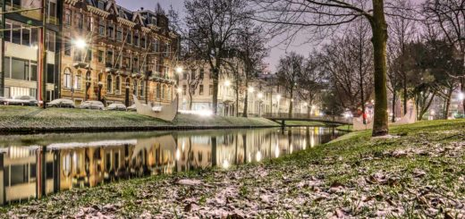 Westersingel canal in Rotterdam in the blue hour before sunset with a very thin layer of snow on the grassy banks