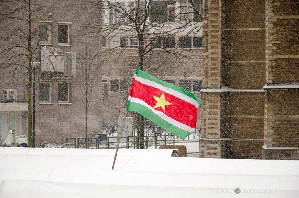 De Surinaamse vlag wappert tijdens een sneeuwbui op de markt op de Binnenrotte in Rotterdam