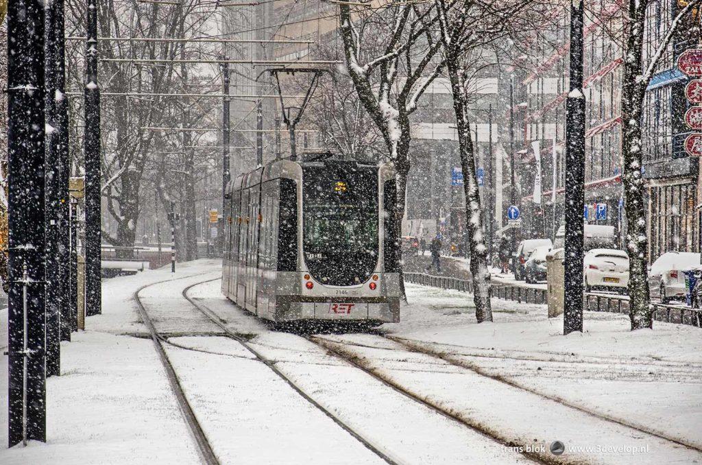 Een tram van de RET rijdt onverstoorbaar door tijdens een sneeuwbui op de Mauritsweg in Rotterdam