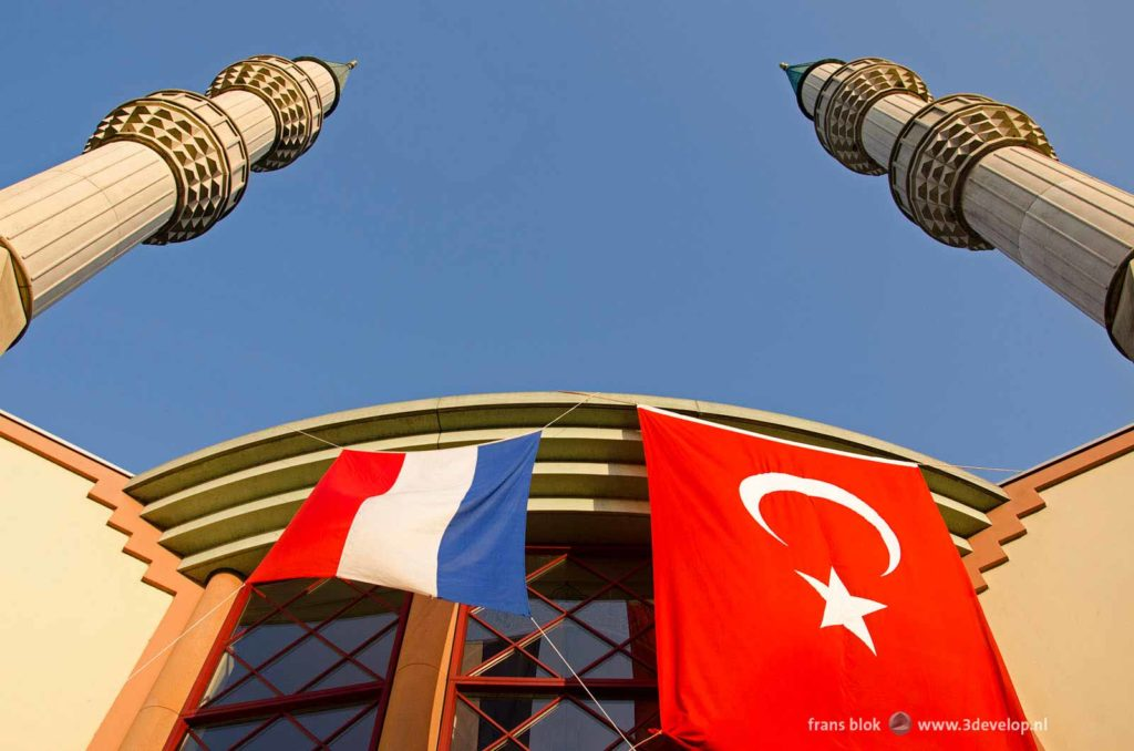 the front facade of the Mevlana mosque in Rotterdam with two minarets and the Dutch and Turkish flag