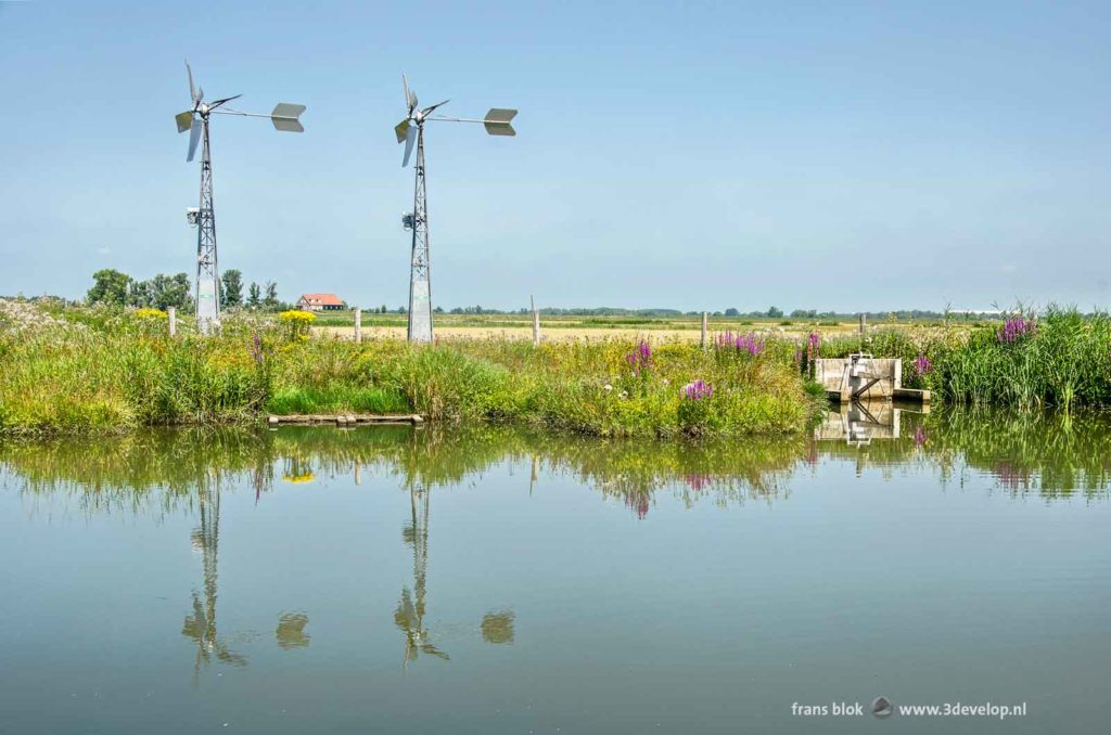 Two steel windmills and a water inlet near a creek in the Noordwaard region of Biesbosch national park in the Netherlands on a sunny summer day