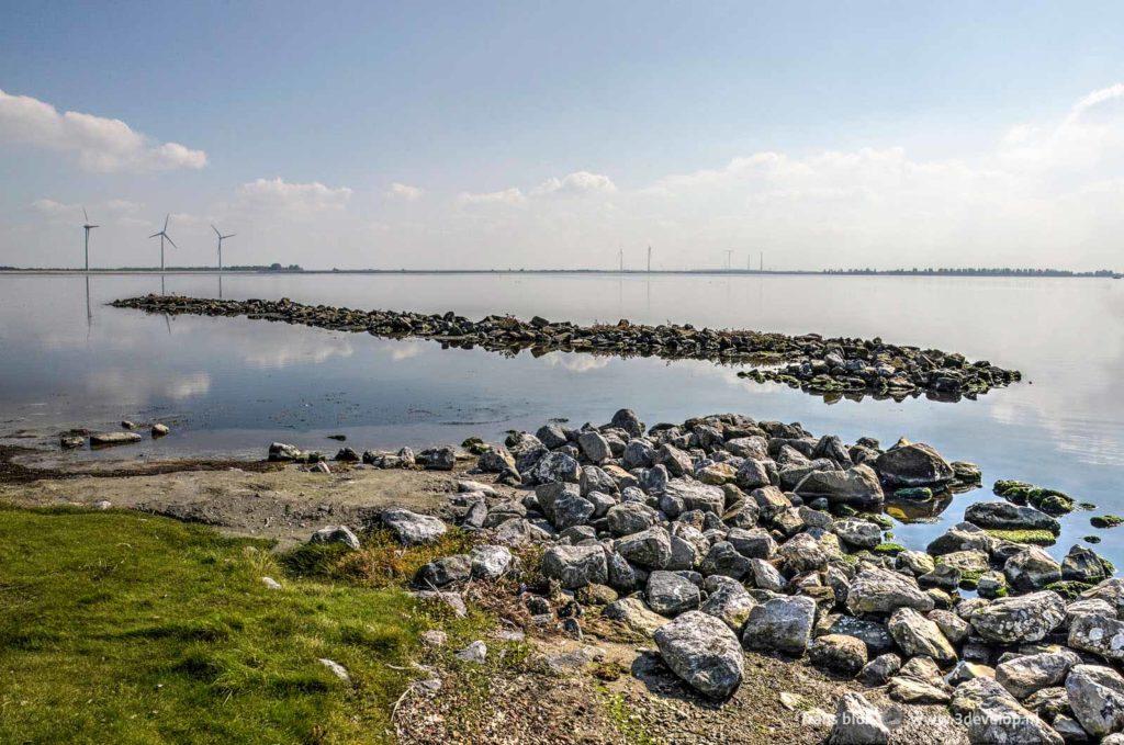 Strandje met zand, gras en stenen in de buurt van Herkingen, gezien tijdens een lange-afstandswandeling rond de Grevelingen