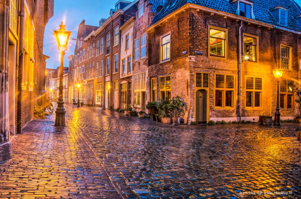 Junction of two narrow, cobble-paved, in the old town of Leyden, The Netherlands, during the blue hour on a rainy night