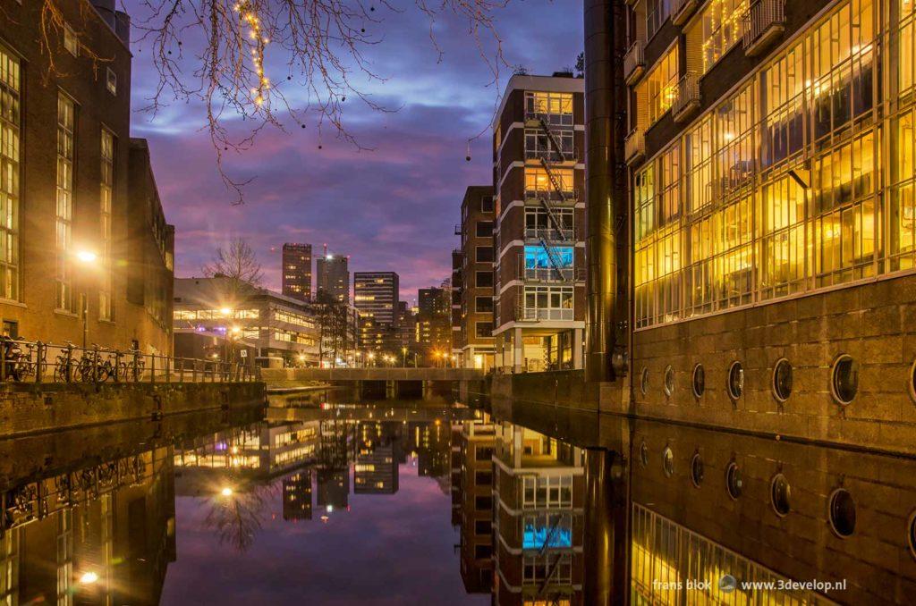Het spiegelgladde water van de Delftsevaart in Rotterdam, met onder andere cafe Dudok onder een langzaam paars kleurende lucht tijdens het ochtendgloren