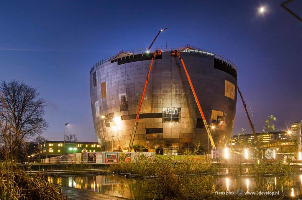 De glimmende pot van het collectiegebouw van museum Boymans in aanbouw in het Museumpark in Rotterdam tijdens het blauwe uur op een ochtend in de winter van 2020