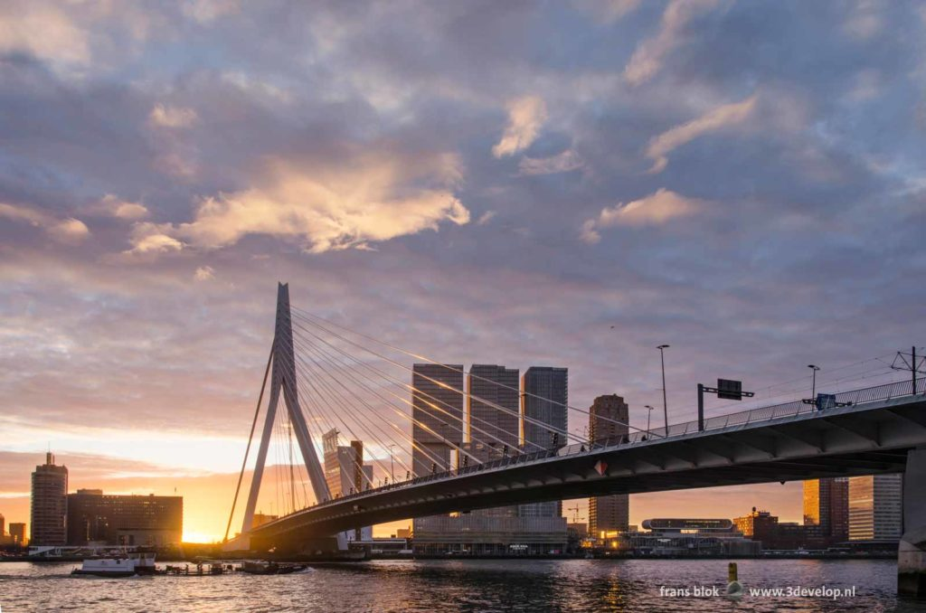 Spectacular sky during sunrise over Erasmus Bridge, the Southbank and the Nieuwe Maas river in Rotterdam on a January morning in 2020