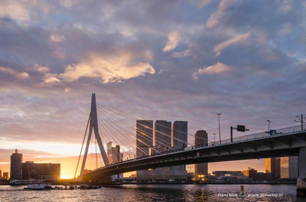 Spectaculaire wolkenlucht tijdens zonsopkomst boven de Erasmusbrug, de Kop van zuid en de Nieuwe Maas in Rotterdam op een ochtend in januari 2020