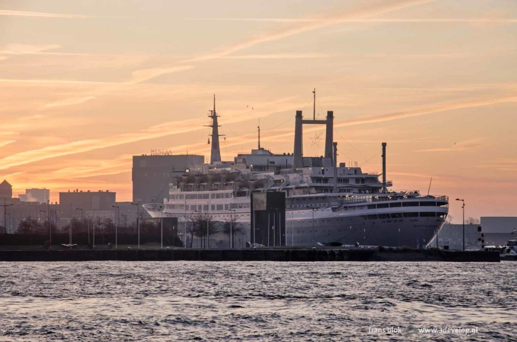 Former cruise ship SS Rotterdam, the eneba grain silo and the Nieuwe Maas river in Rotterdam at sunrise under a beautiful sky with contrails