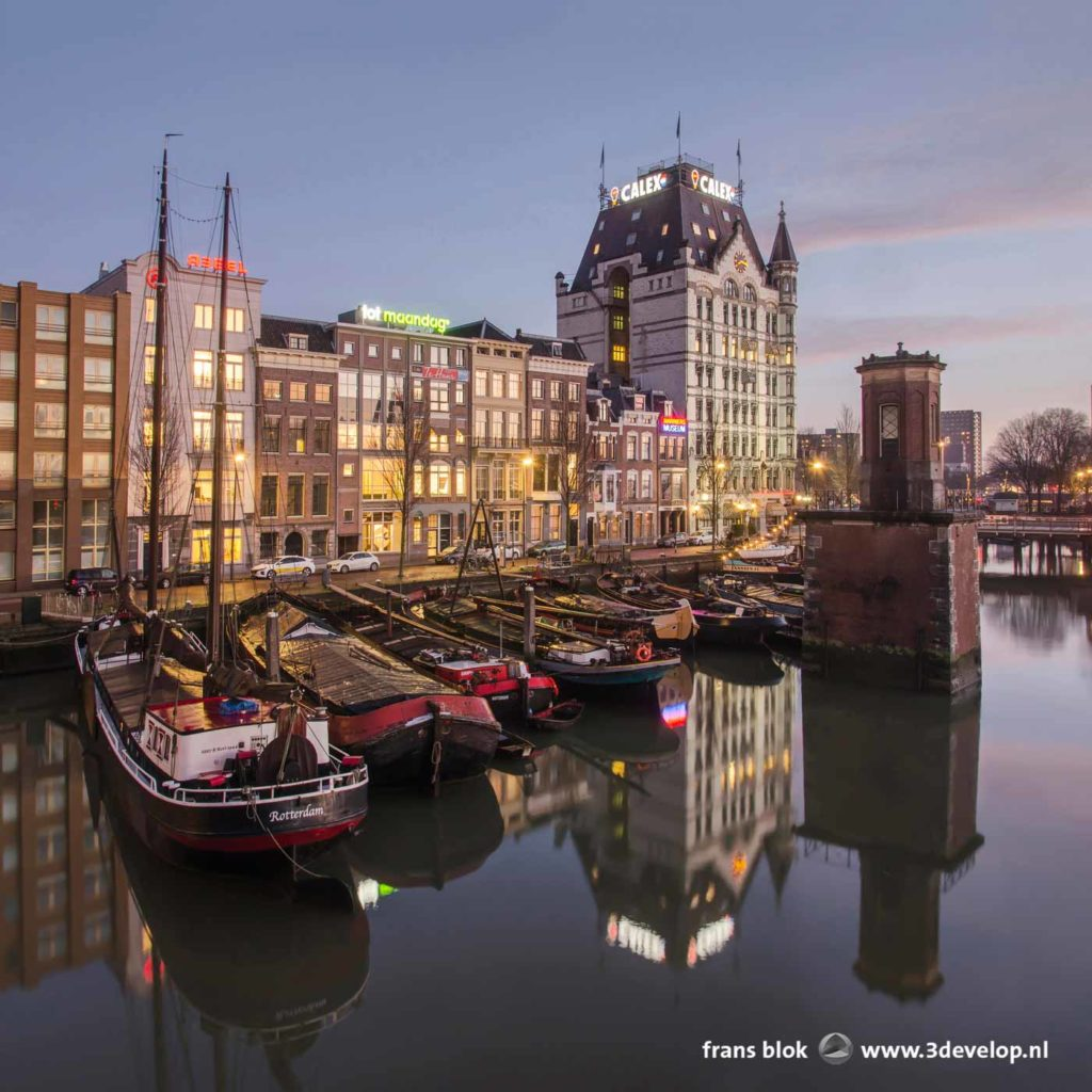 Het Witte Huis en andere havenpanden en een aantal historische binnenvaartschepen weerspiegelen in het gladde water van de Wijnhaven in Rotterdam op een vroege ochtend in januari 2020