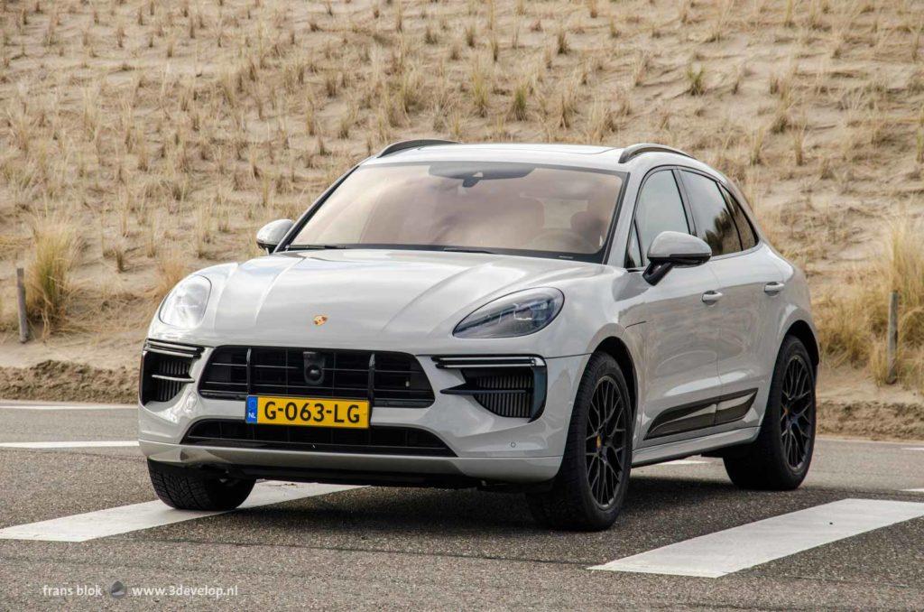 Een krijtwitte Porsche Macan Turbo, op het asfalt van een parkeerplaats bij de duinen op de Maasvlakte bij Rotterdam
