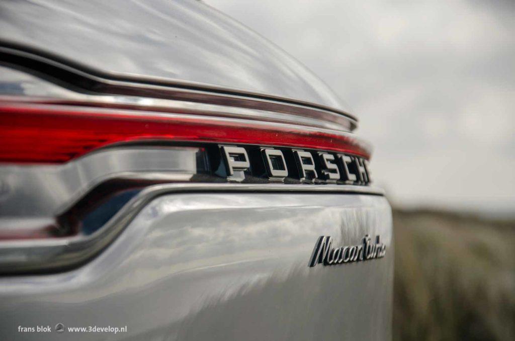 Close up van de achterkant van een zilvergrijze Posche Macan Turbo tegen een vage achtergrond