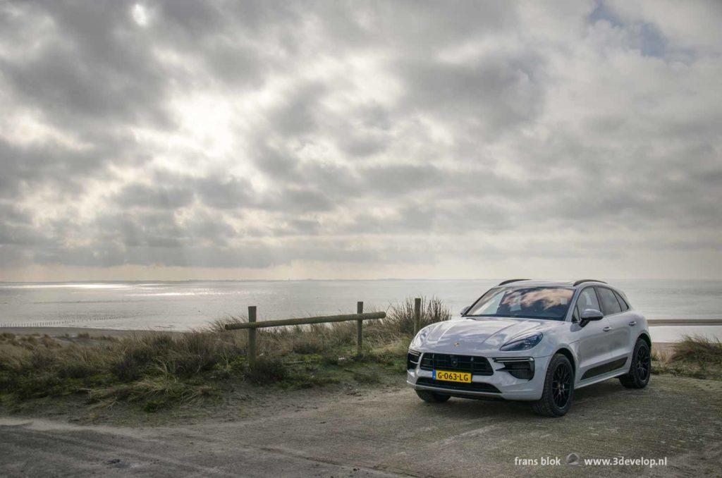 Zilvergrijze Porsche Macan Turbo geparkeerd op de Maasvlakte bij Rotterdam met de zee en een spectaculaire wolkenlucht op de achtergrond