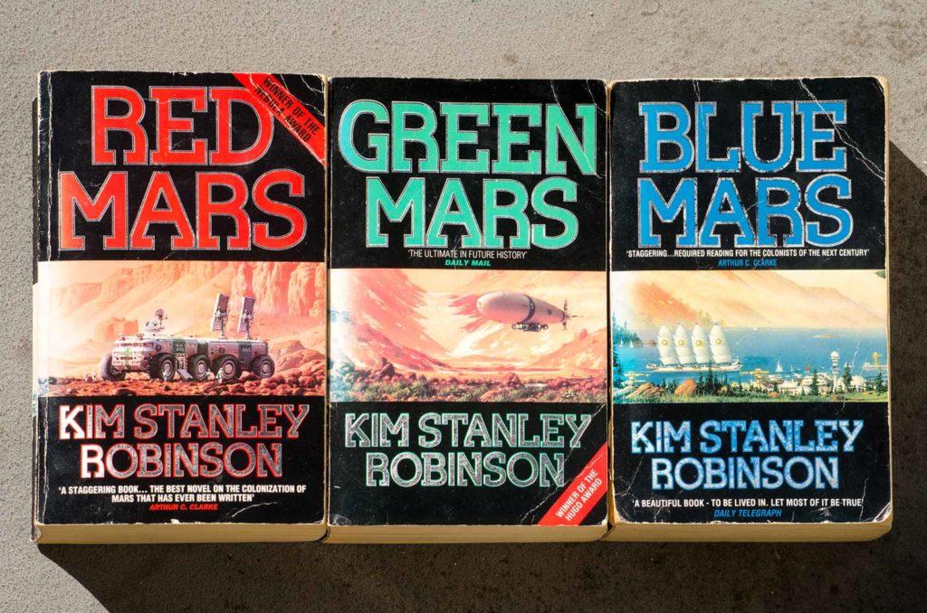 Enigszins stukgelezen exemplaren van Kim Stanley Robinson's trilogie Red Mars, Green Mars en Blue Mars