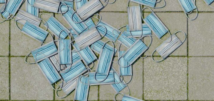 Detail van een wereldkaart opgebouwd uit mondkapje, achteloos achtergelaten op het trottoir, met duidelijk herkenbaar de vorm van Noord-Amerika