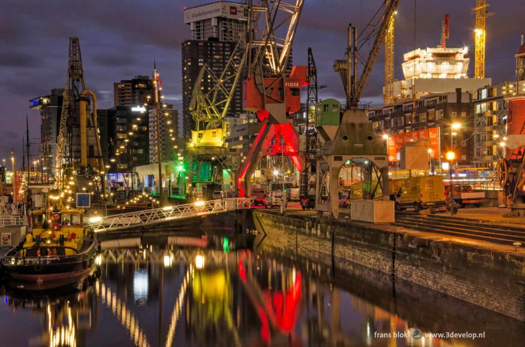 Colorful photo with harbour and construction cranes at Leuvehaven harbour in Rotterdam, The Netherlands during the blue hour on a winter morning