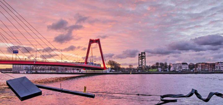 De Nieuwe Maas, de Waslijn, de Willemsbrug en het Noordereiland in Rotterdam onder een spectaculaire lucht bij zonsopkomst